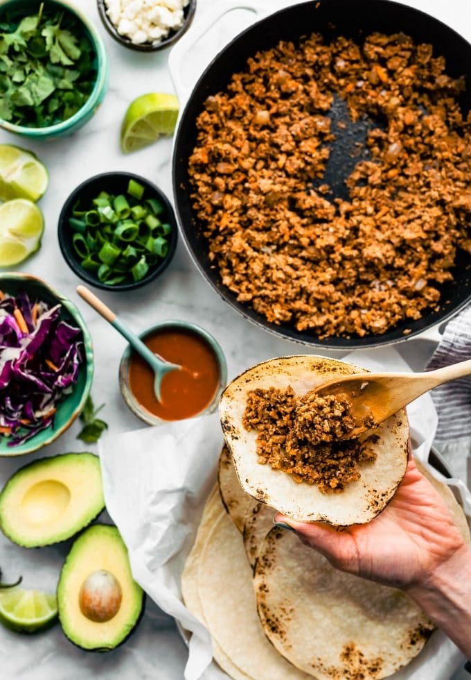 Overhead tabletop image of vegan tacos being prepared with vegan taco meat. Taco toppings including avocado, slaw, limes, cilantro, and green onions can also be seen.