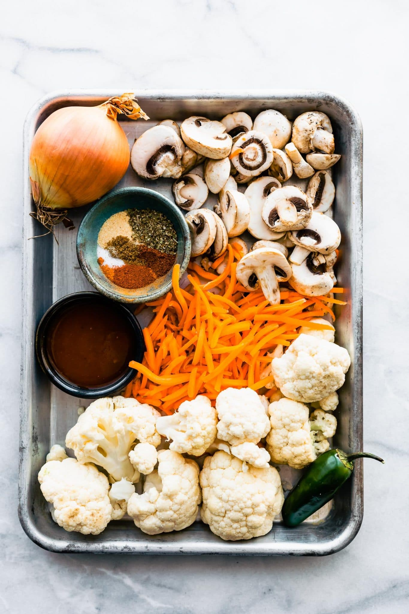 Overhead image of a sheet pan with ingredients for vegan taco meat including: yellow onion, mushrooms, spices, shredded carrots, cauliflower florets, and jalapeno.