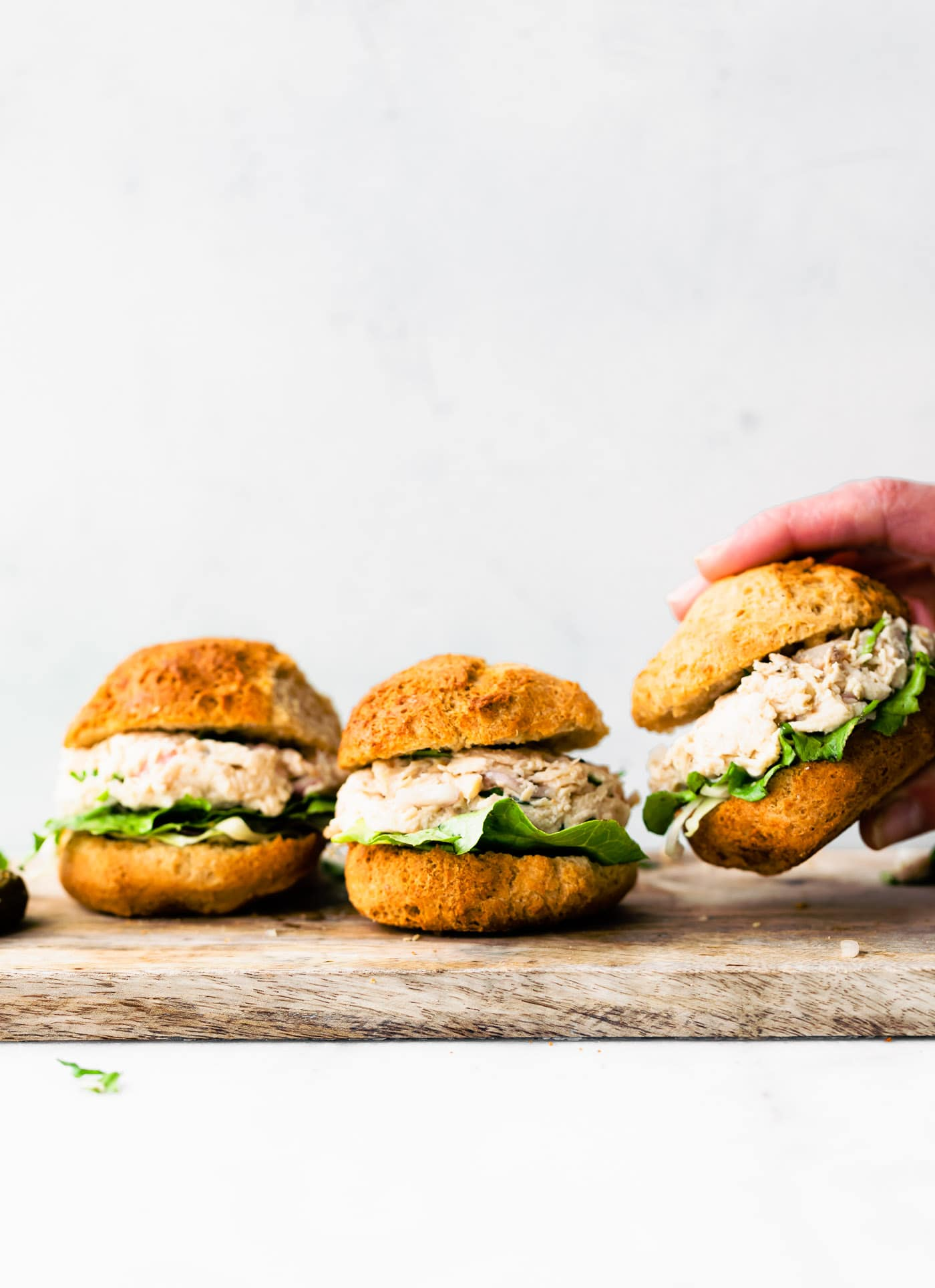 Side image of three chicken salad sandwiches.