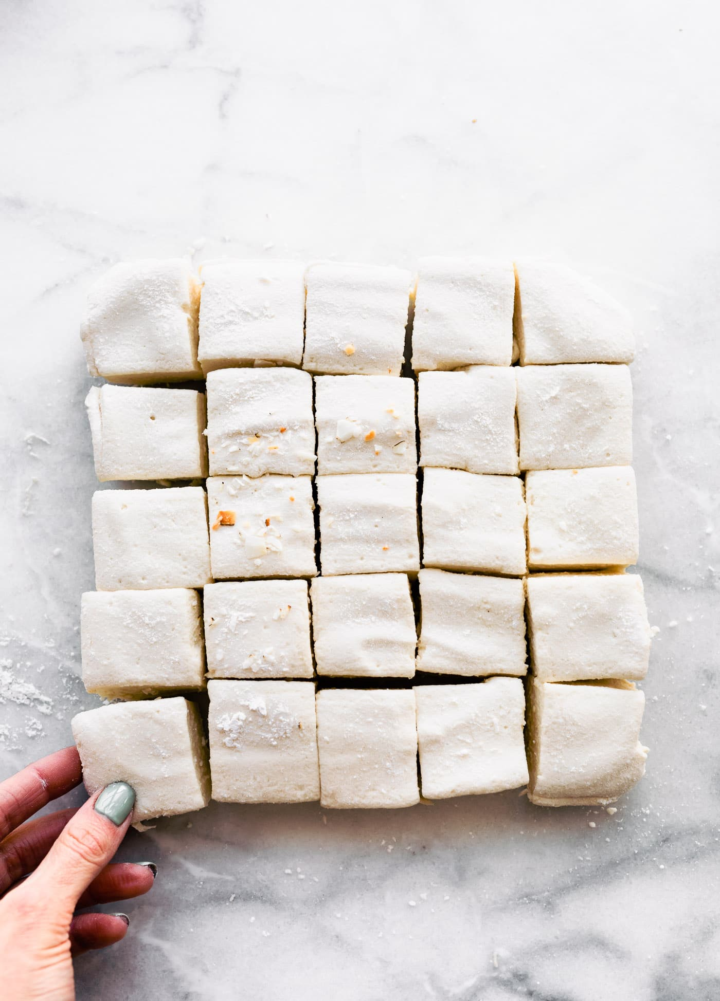 Overhead image of homemade marshmallows cut into 1-1/2 inch squares. Hand is pulling one away.