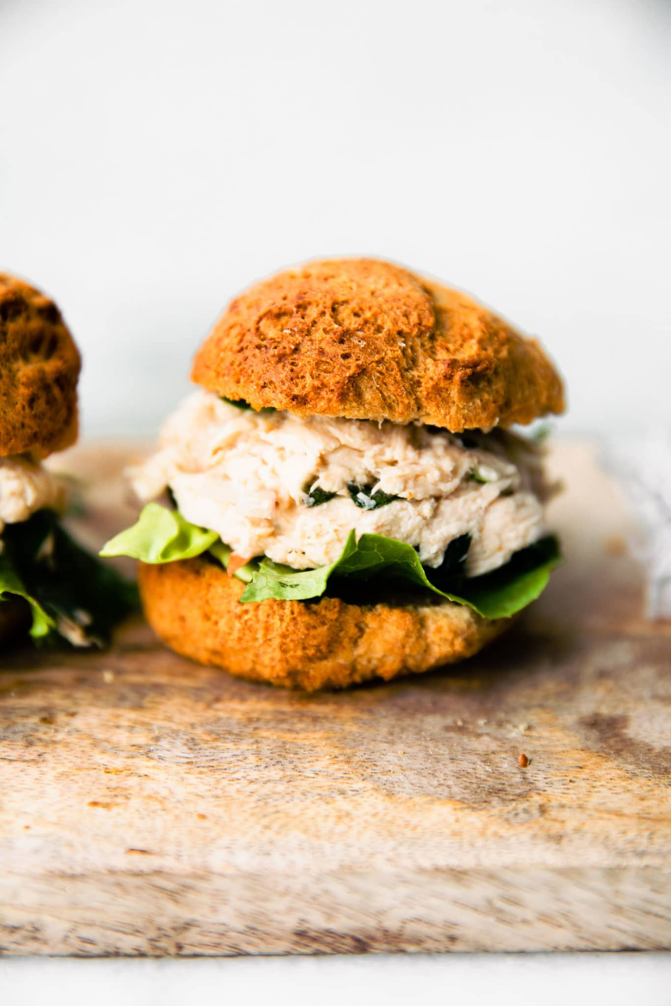 Side image of crock pot chicken salad on a gluten-free roll with lettuce.
