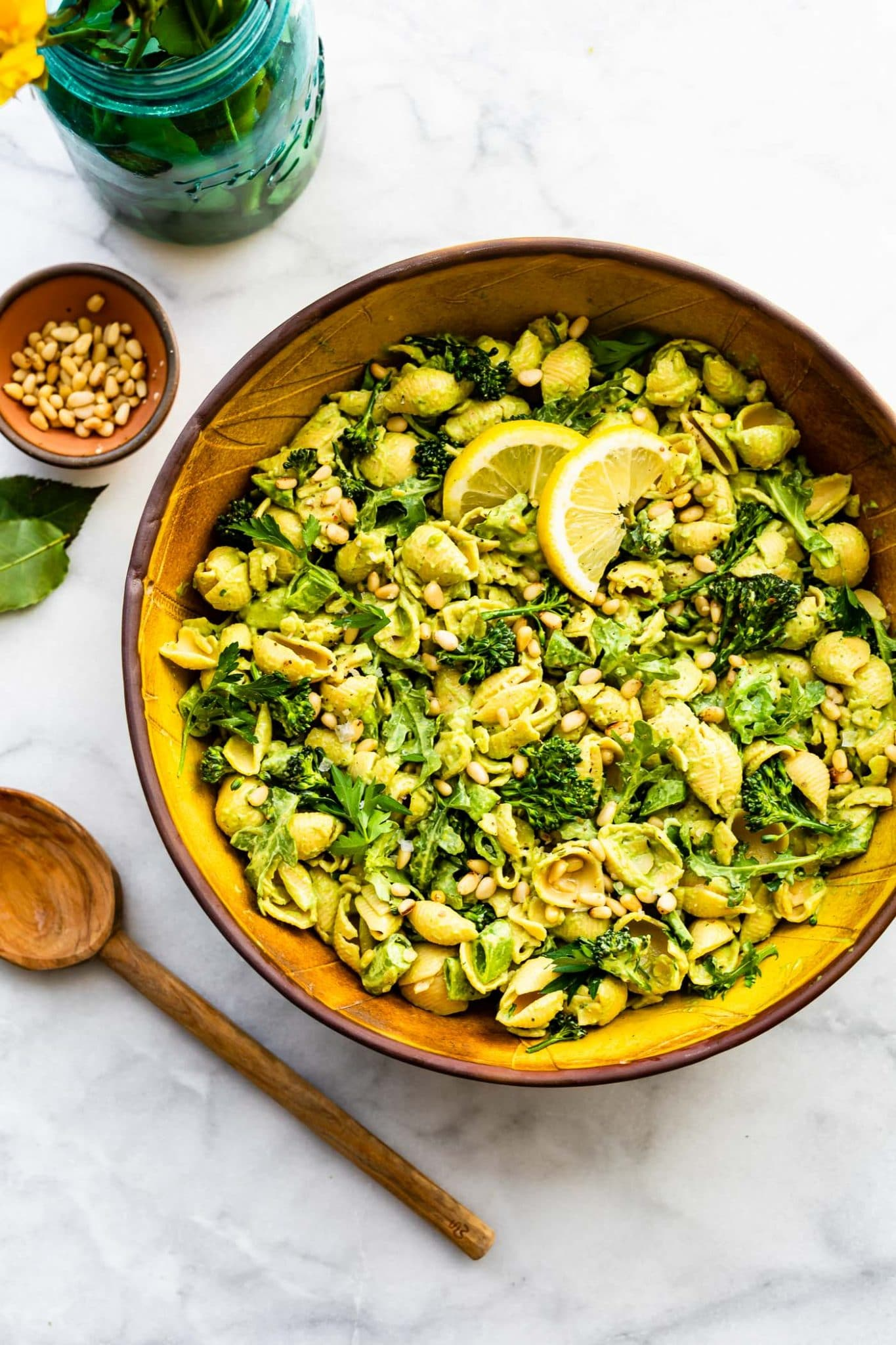 Overhead image of vegan green goddess pasta salad with spoon and flowers.