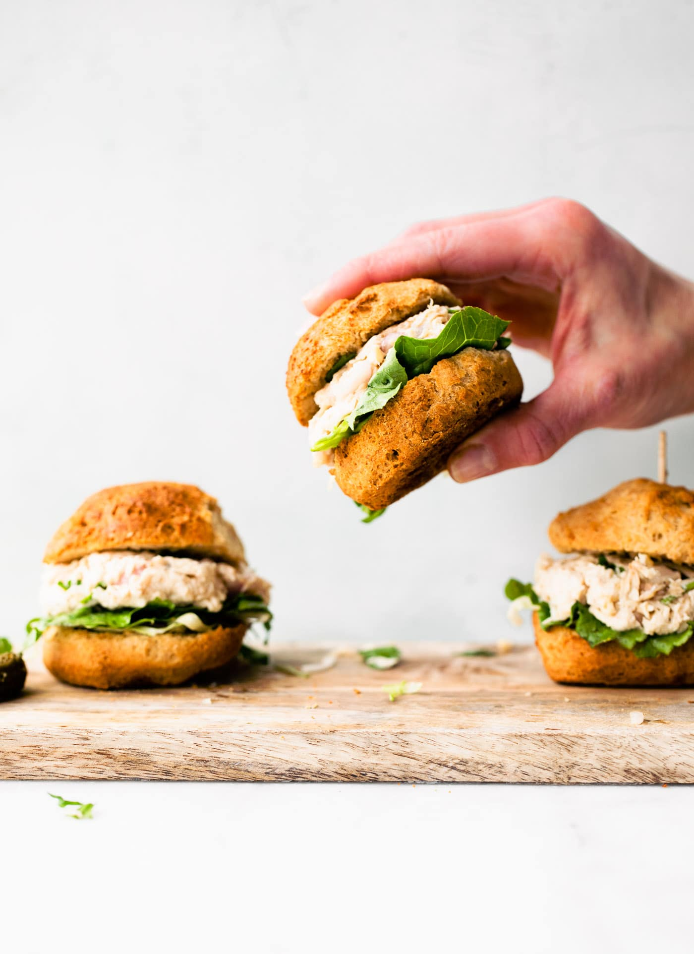 Side shot of chicken sliders being lifted from a cutting board.