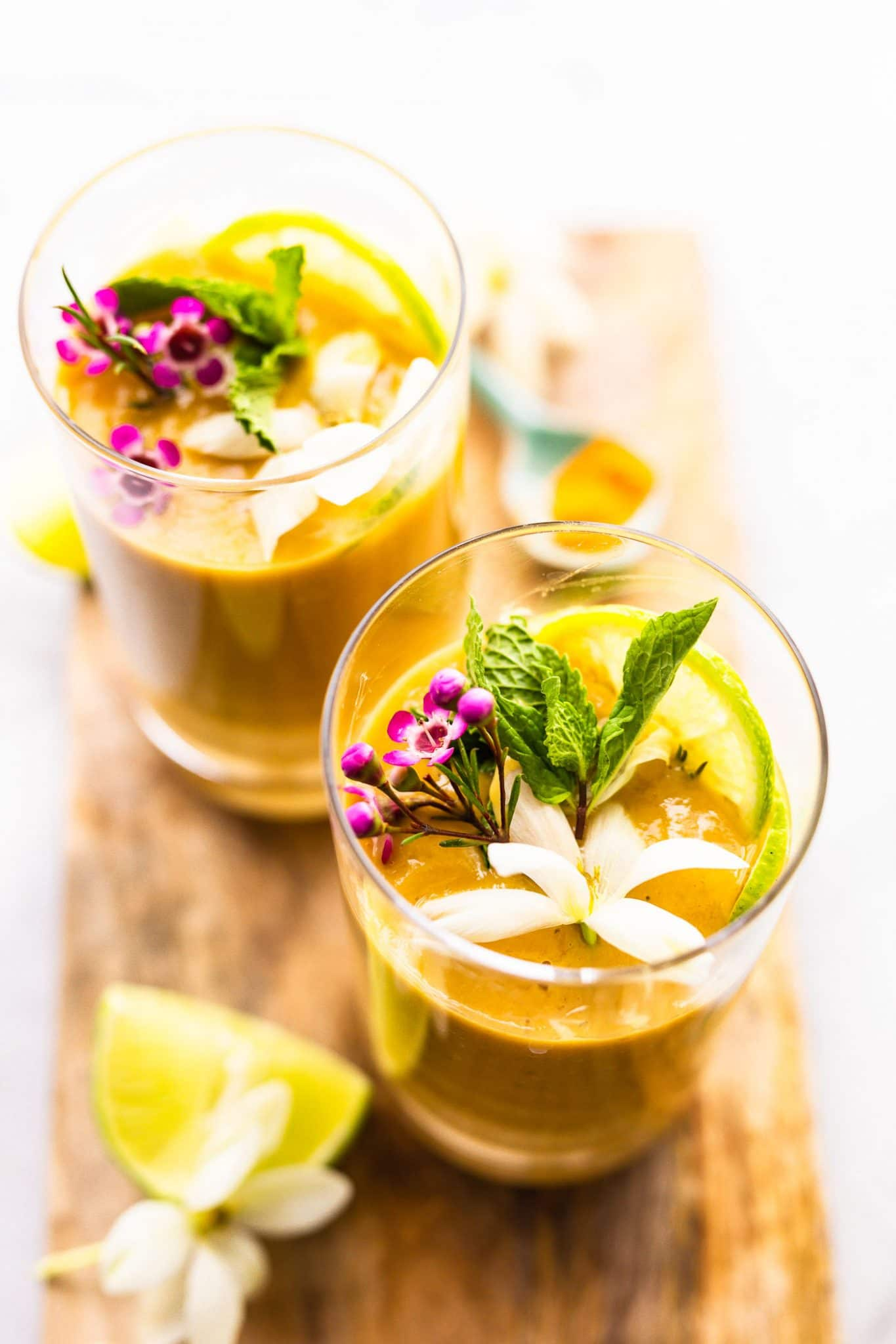 Overhead image of two turmeric smoothies on a serving platter, garnished with fresh flowers, limes, and mint.