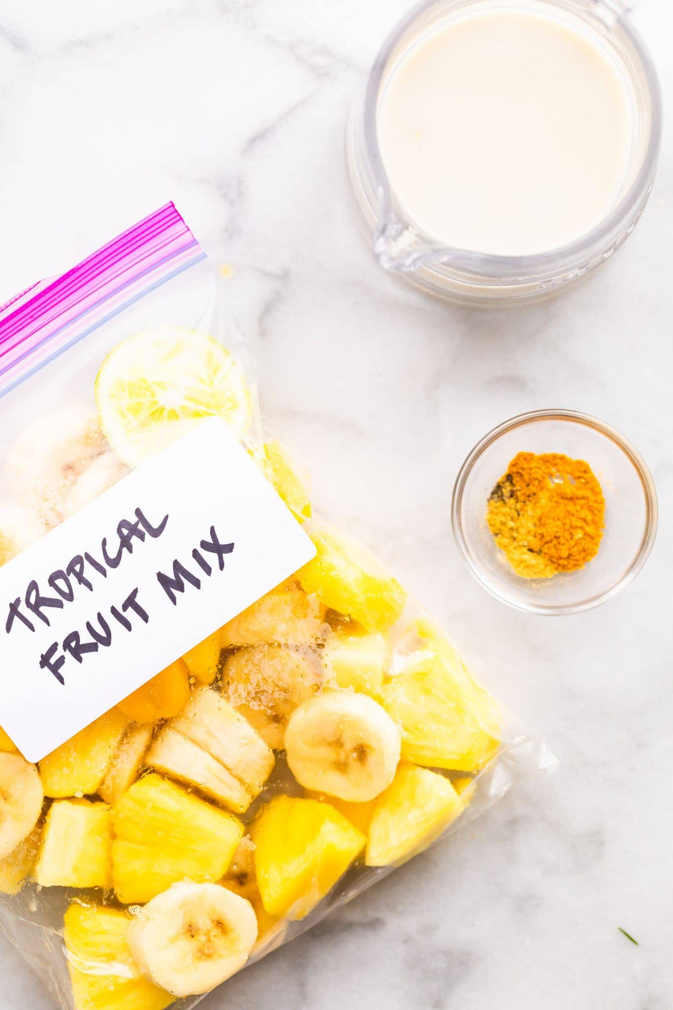 Overhead image of frozen fresh fruit in a ziploc bag next to spices and non-dairy milk for a turmeric smoothie.