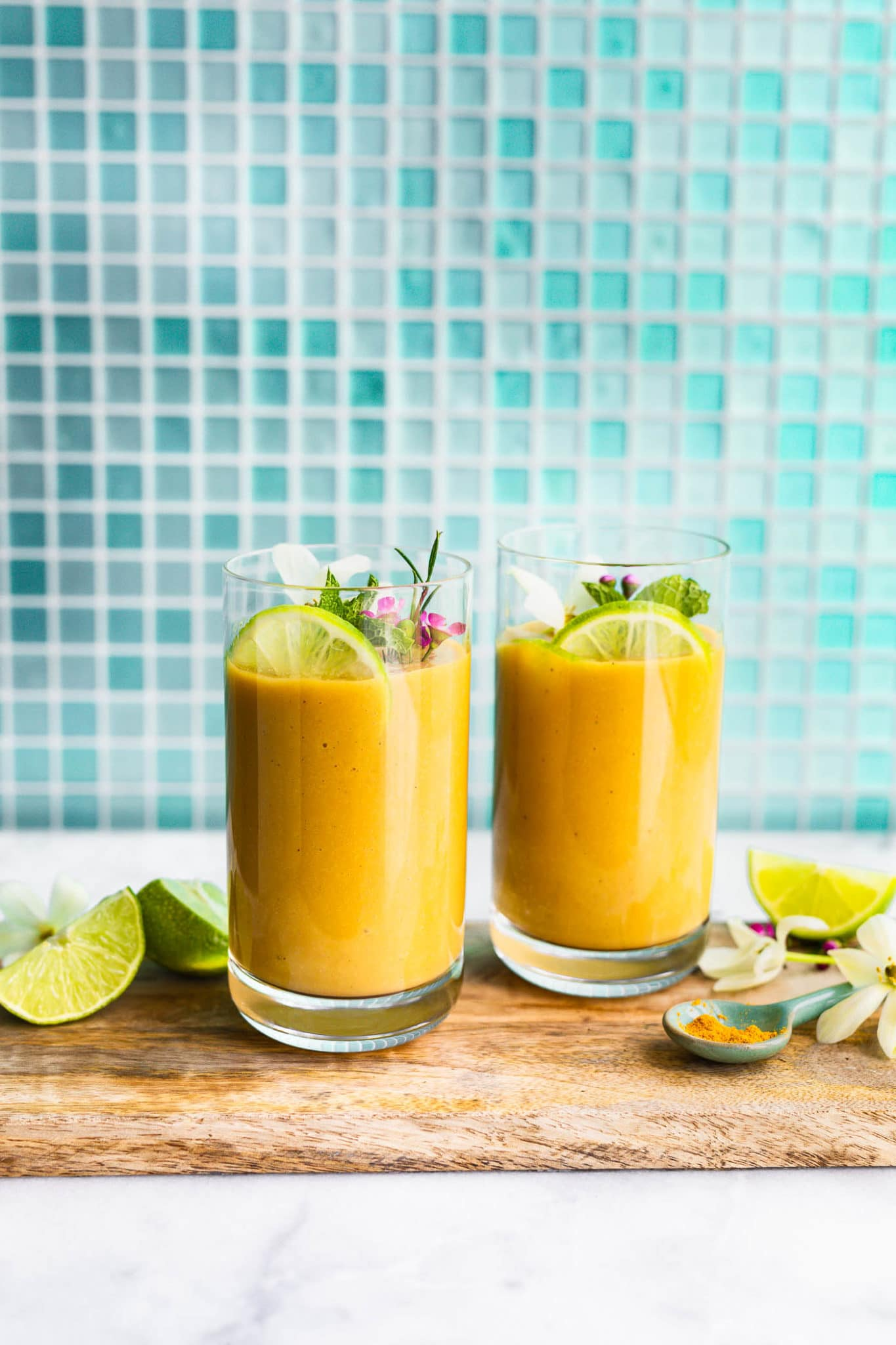 A side shot of two turmeric smoothies in glasses on a serving tray with a garnish of lime, mint, and flowers.