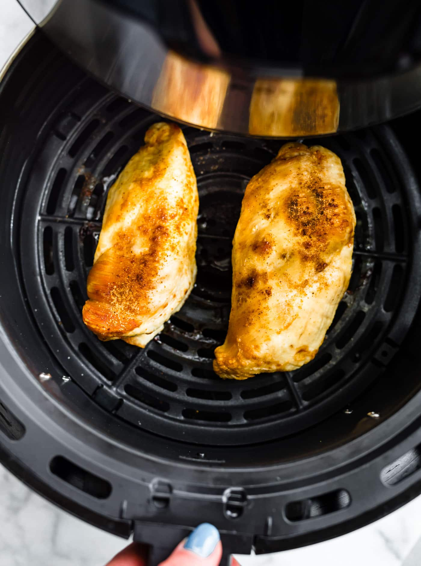 Overhead image of chicken breasts in the air fryer.