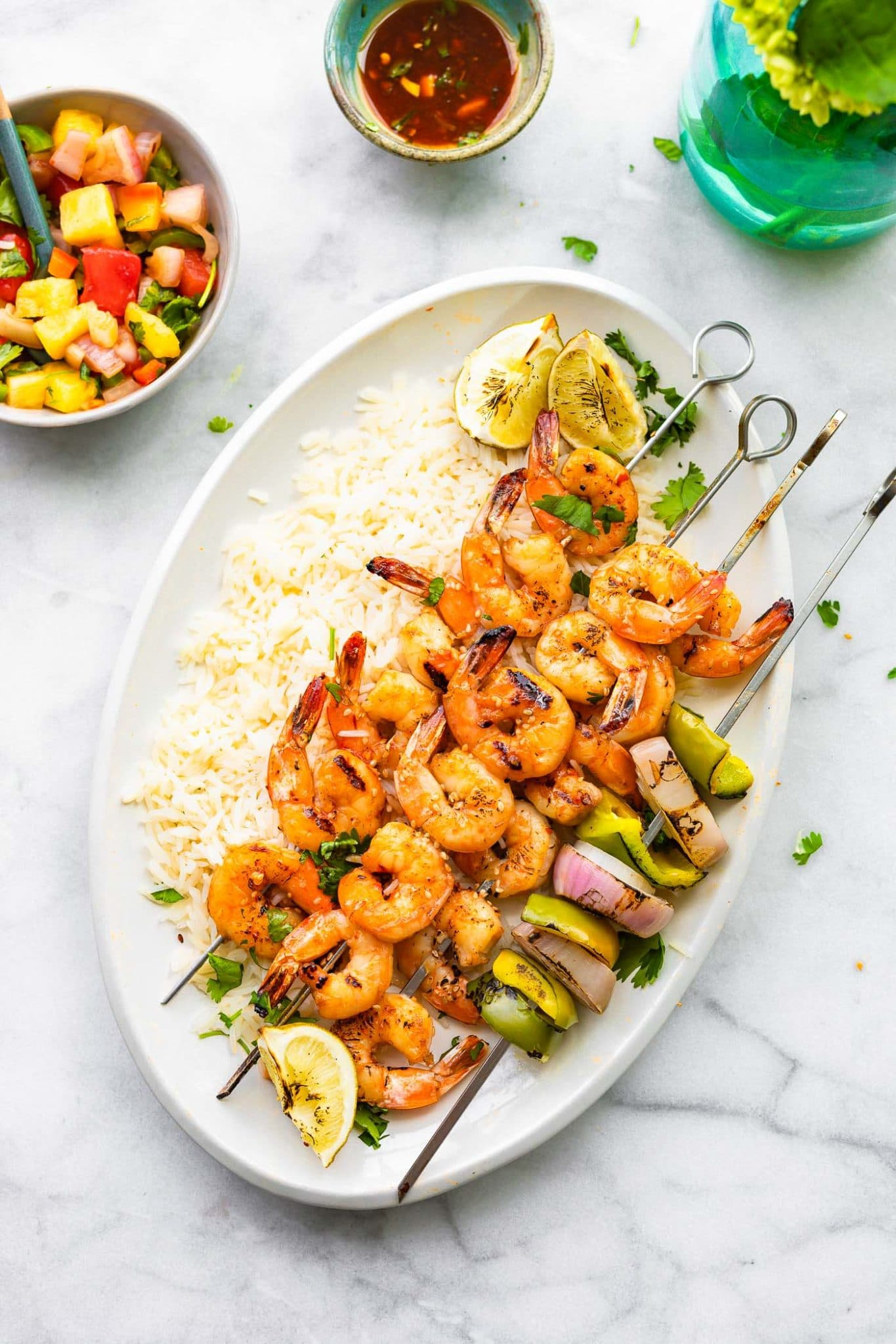 Overhead image of grilled skewered shrimp on a platter of rice with a side of watermelon salsa.