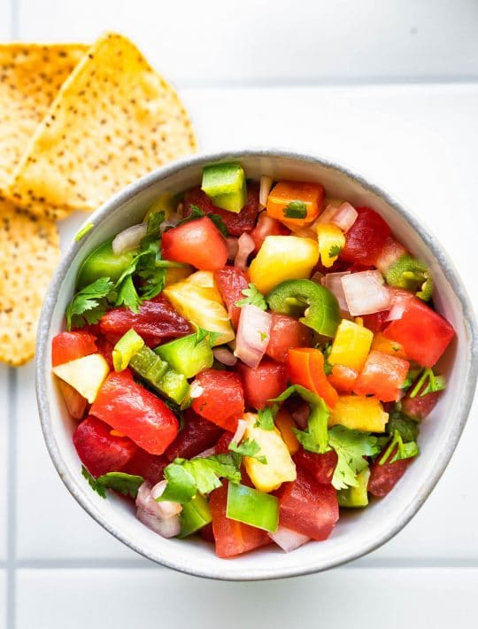 overhead image of pineapple salsa in a small bowl with chips on the side