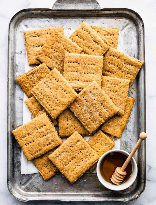 Overhead image of gluten free graham crackers on a sheet pan with honey.