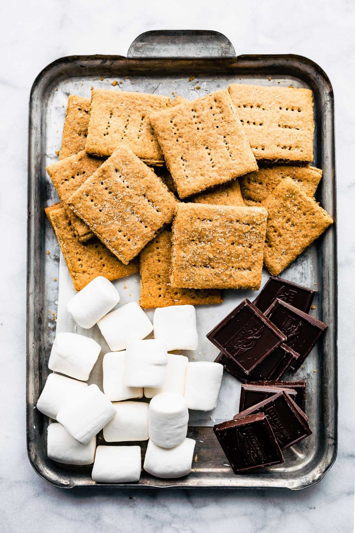Overhead image of sheet pan with homemade graham crackers, dark chocolate, and vegan marshmallows in piles.
