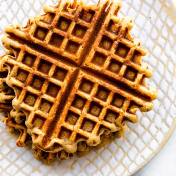 overhead photo of stack of waffles on white textured plate