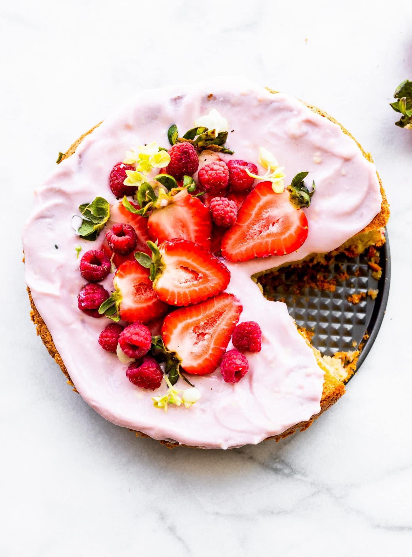 Overhead image of flourless almond cake dressed with yogurt frosting, fresh berries, and edible flowers.