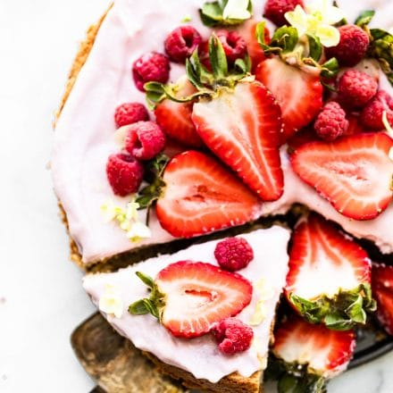 Overhead image of almond cake with berry frosting with a slice being removed.