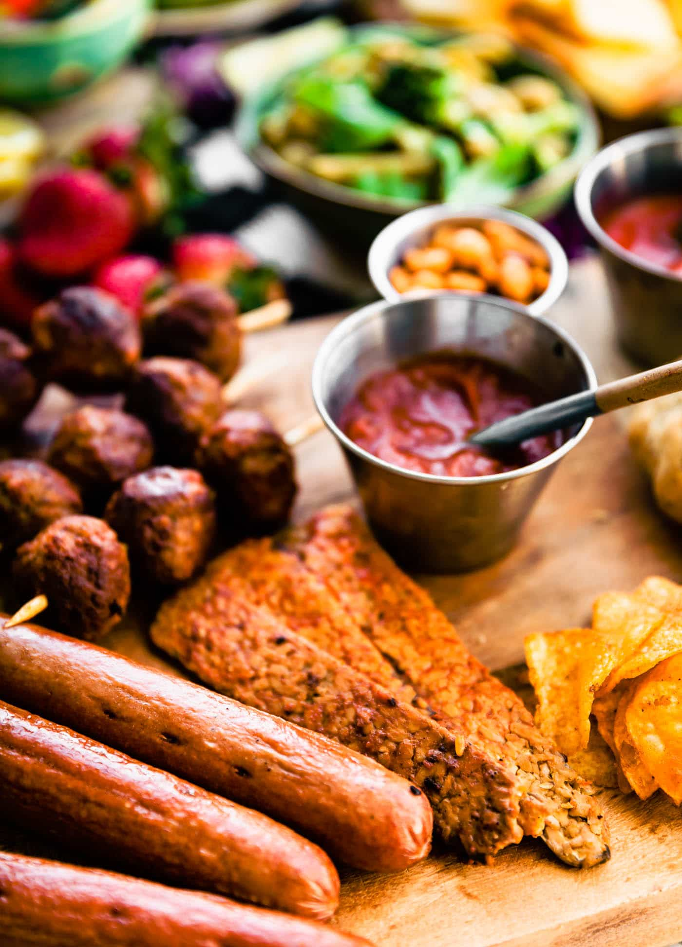 Close up image of recipes included in the summer bbq graze board such as sausage, homemade sriracha, meatballs, and homemade crackers.