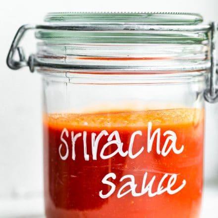 Side view of sriracha sauce in a glass mason jar.