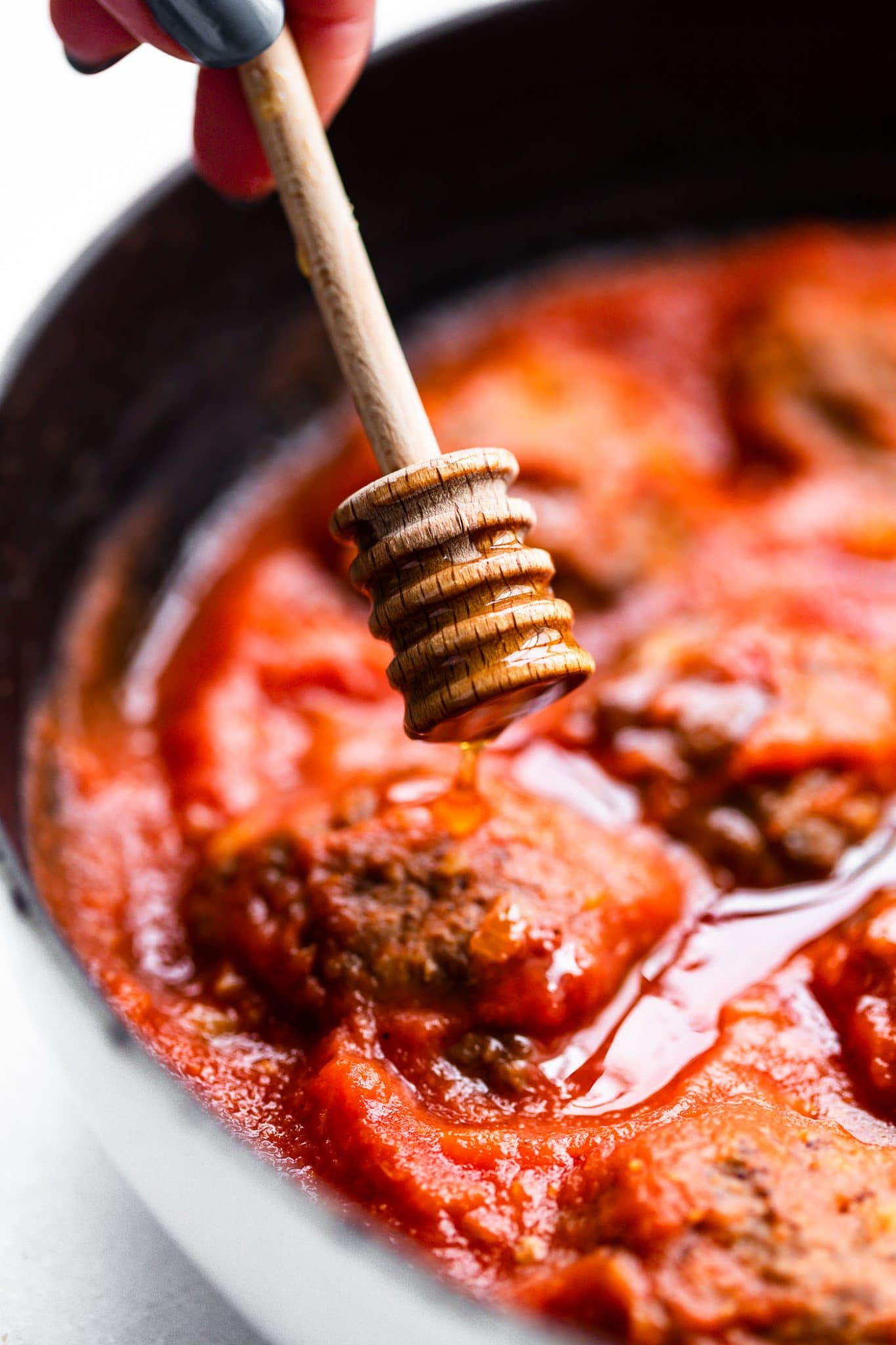 Close up image of honey being drizzled into meatballs and sauce.