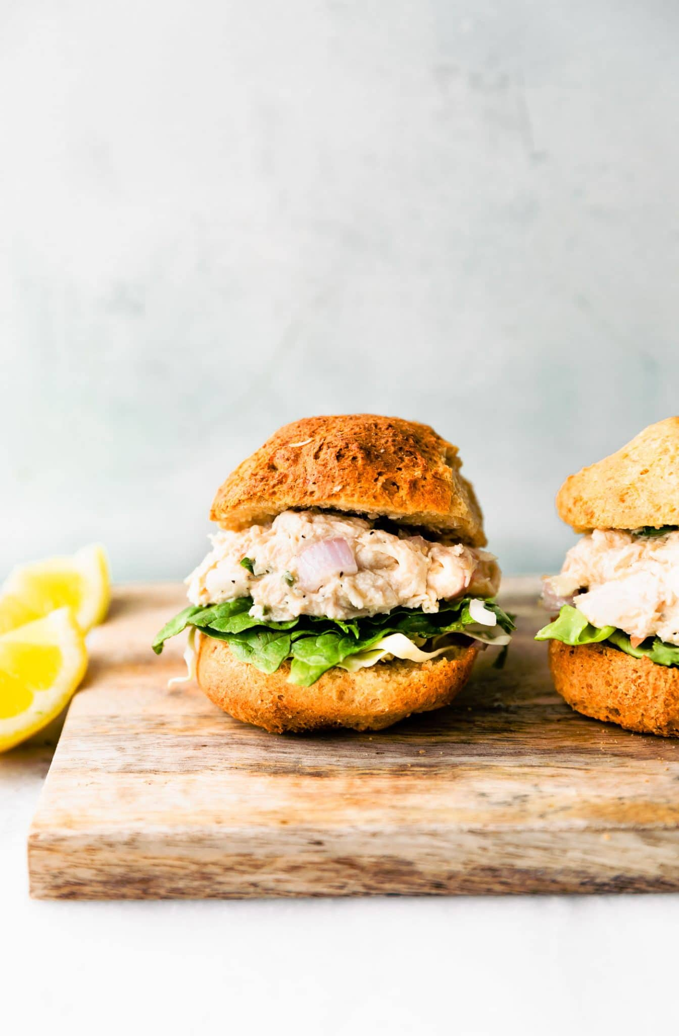 Side close up image of a chicken salad sandwich on a cutting board garnished with lemon.