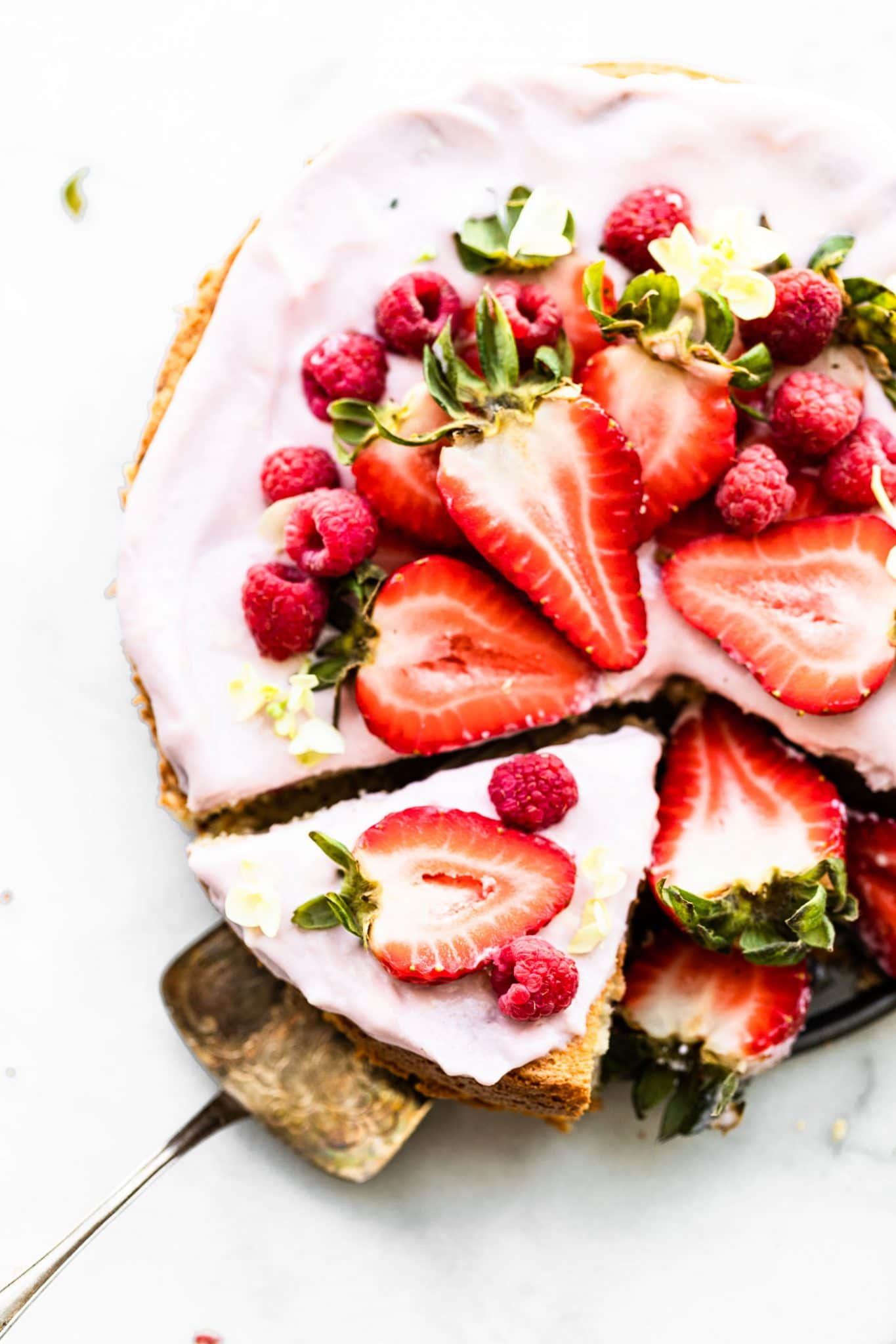 Overhead close up image of almond cake with berry frosting, garnished with fresh berries.