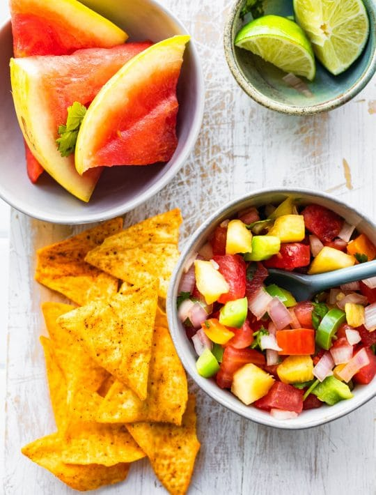 overhead image of watermelon pineapple salsa next to chips, limes, and more watermelon