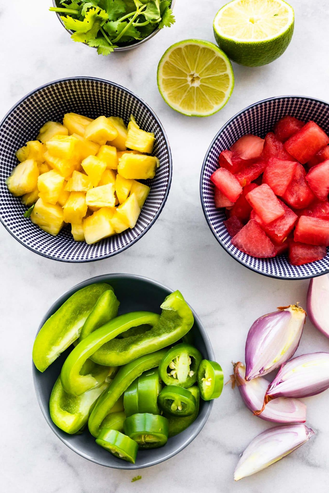 overhead image of ingredients for watermelon pineapple salsa in bowls on the table.