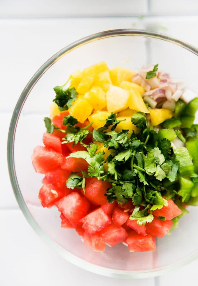 overhead process image of watermelon pineapple salsa in a glass bowl.