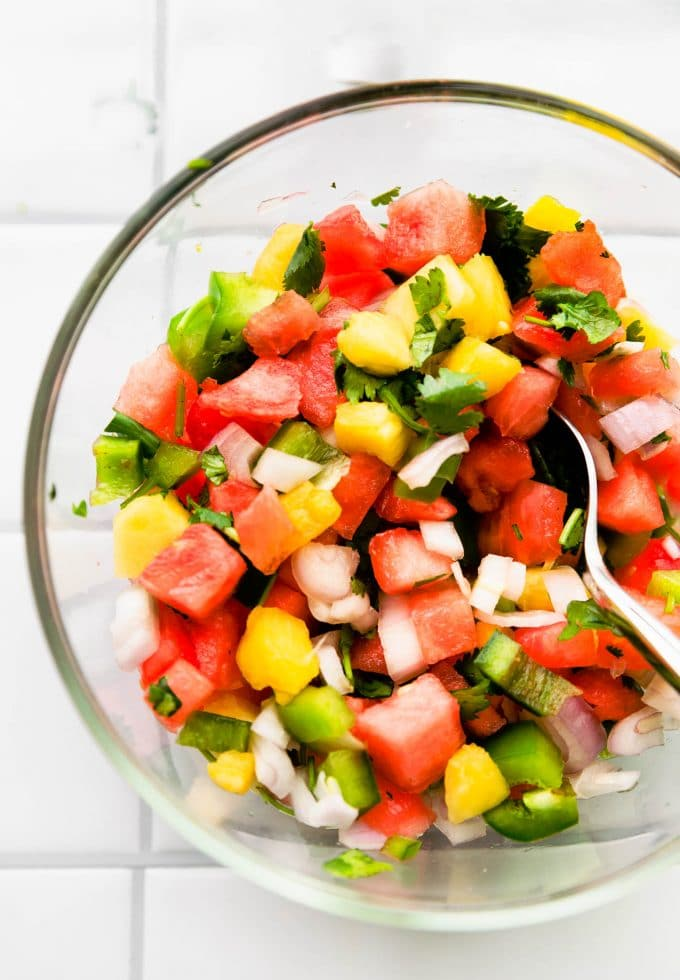 overhead image of watermelon pineapple salsa in a bowl with a spoon