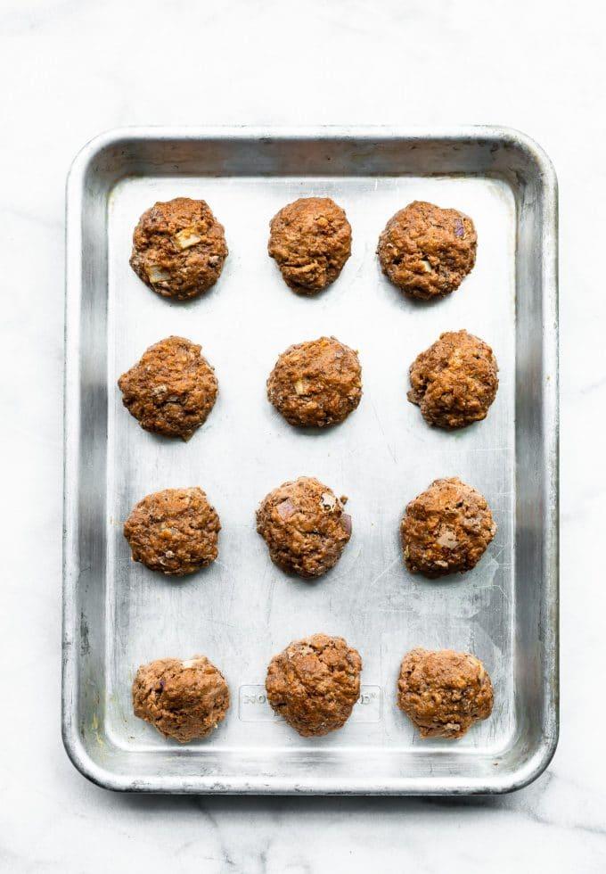Overhead image of meatballs on a sheet pan.