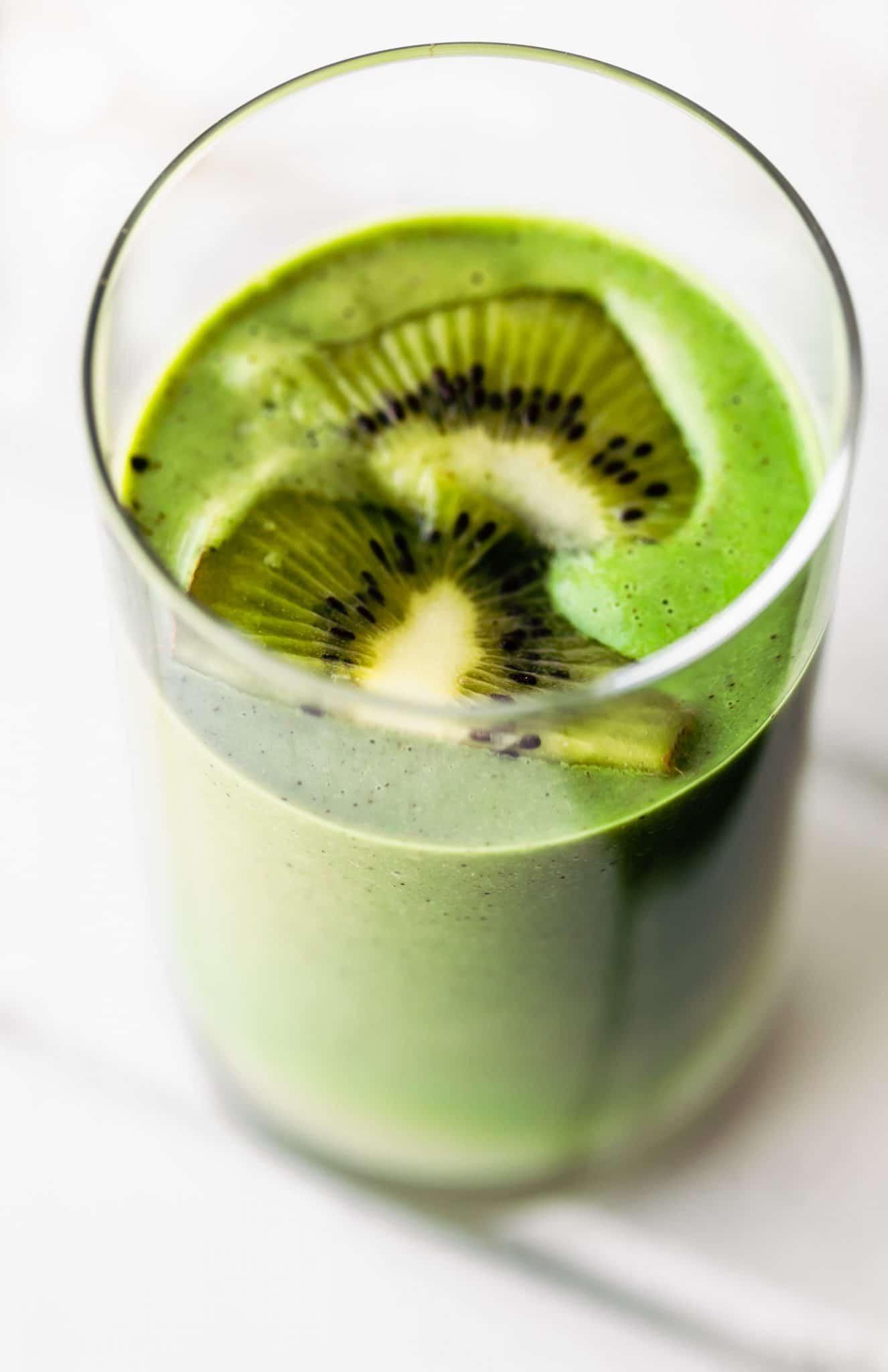 Close up image of superfood spirulina smoothie garnished with fresh kiwi.