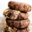 Close up stack of vegan chocolate breakfast cookies with melted chocolate and crushed hazelnuts.