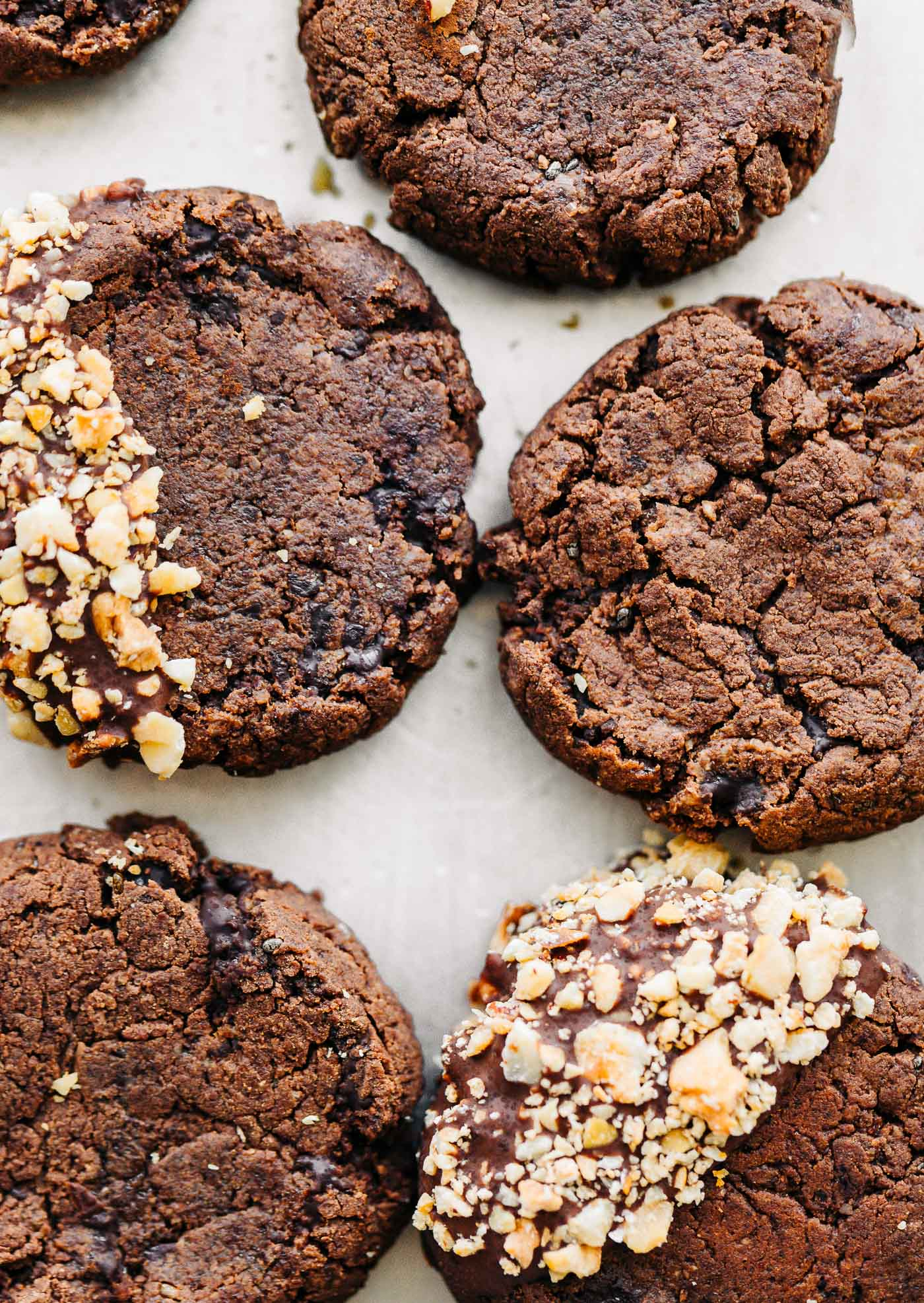 overhead shot of small chocolate nut cookies on white baking parchment paper.