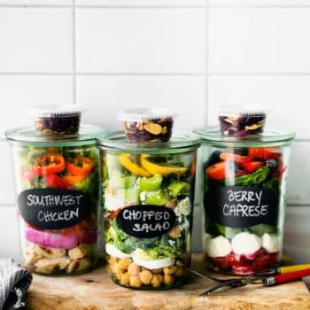 Close up image of three mason jar salads with mariani salad toppers.