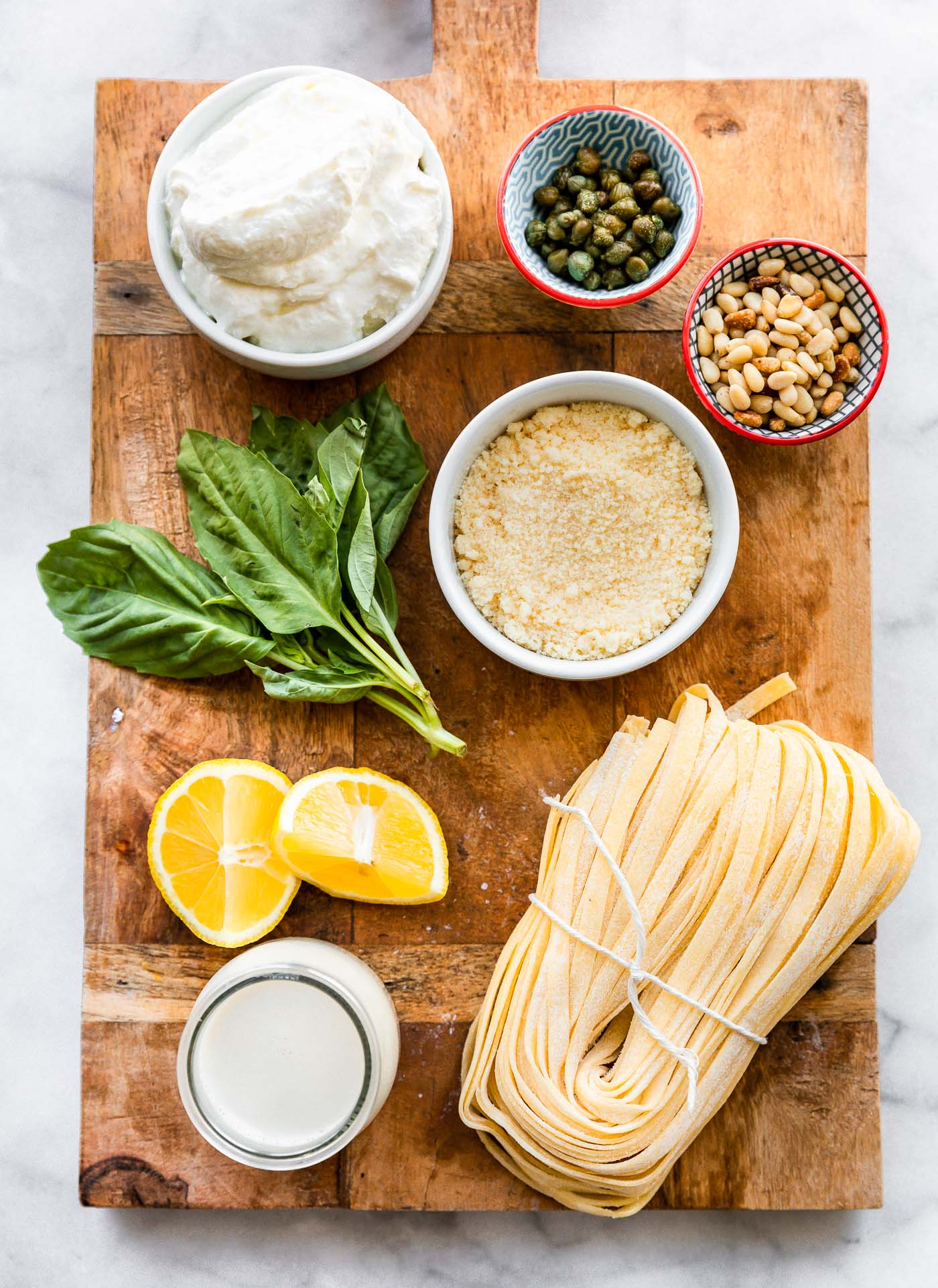 Ingredients on a cutting board for homemade fettuccine alfredo