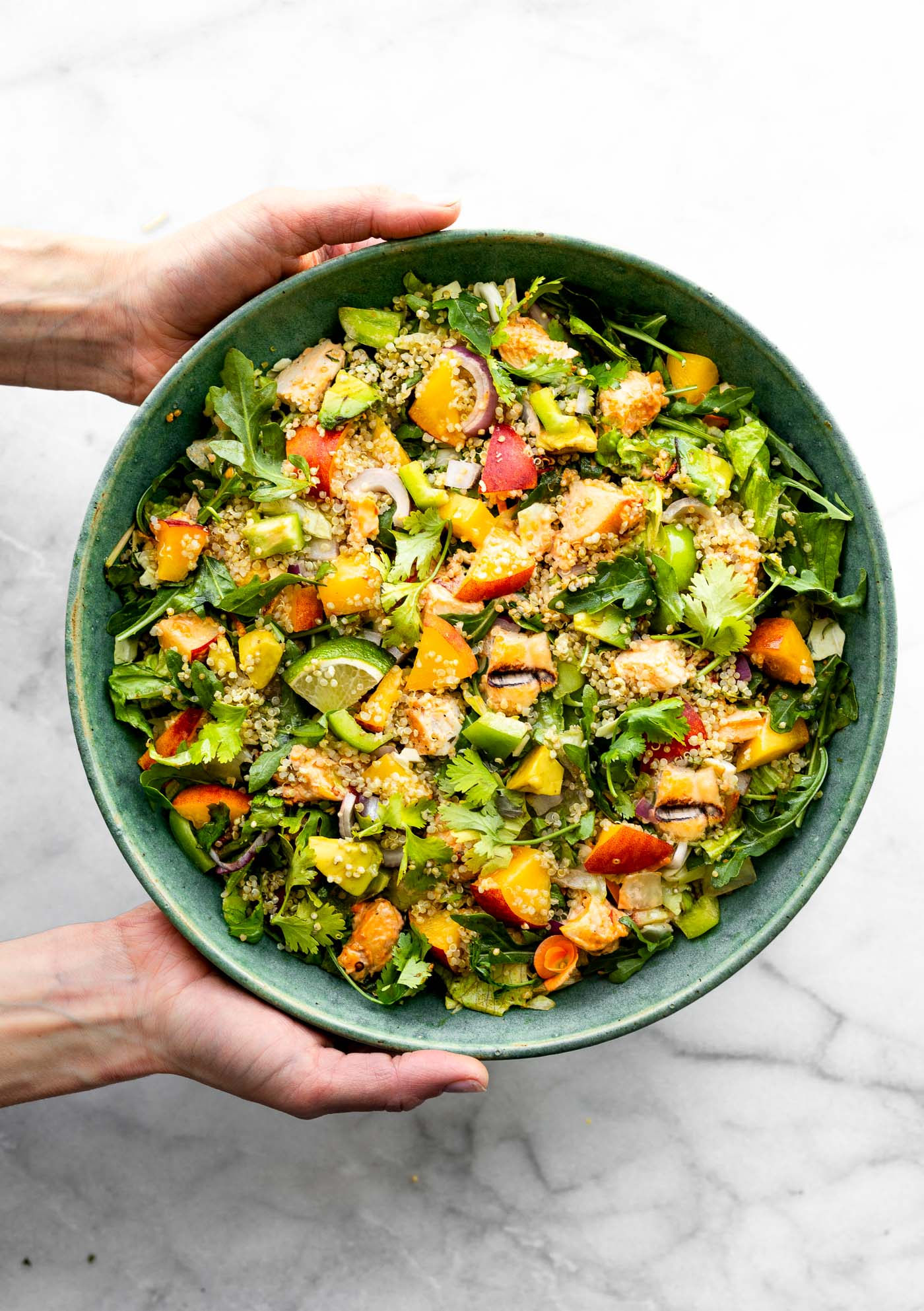 two hands presenting a large serving bowl of peach chipotle chicken salad