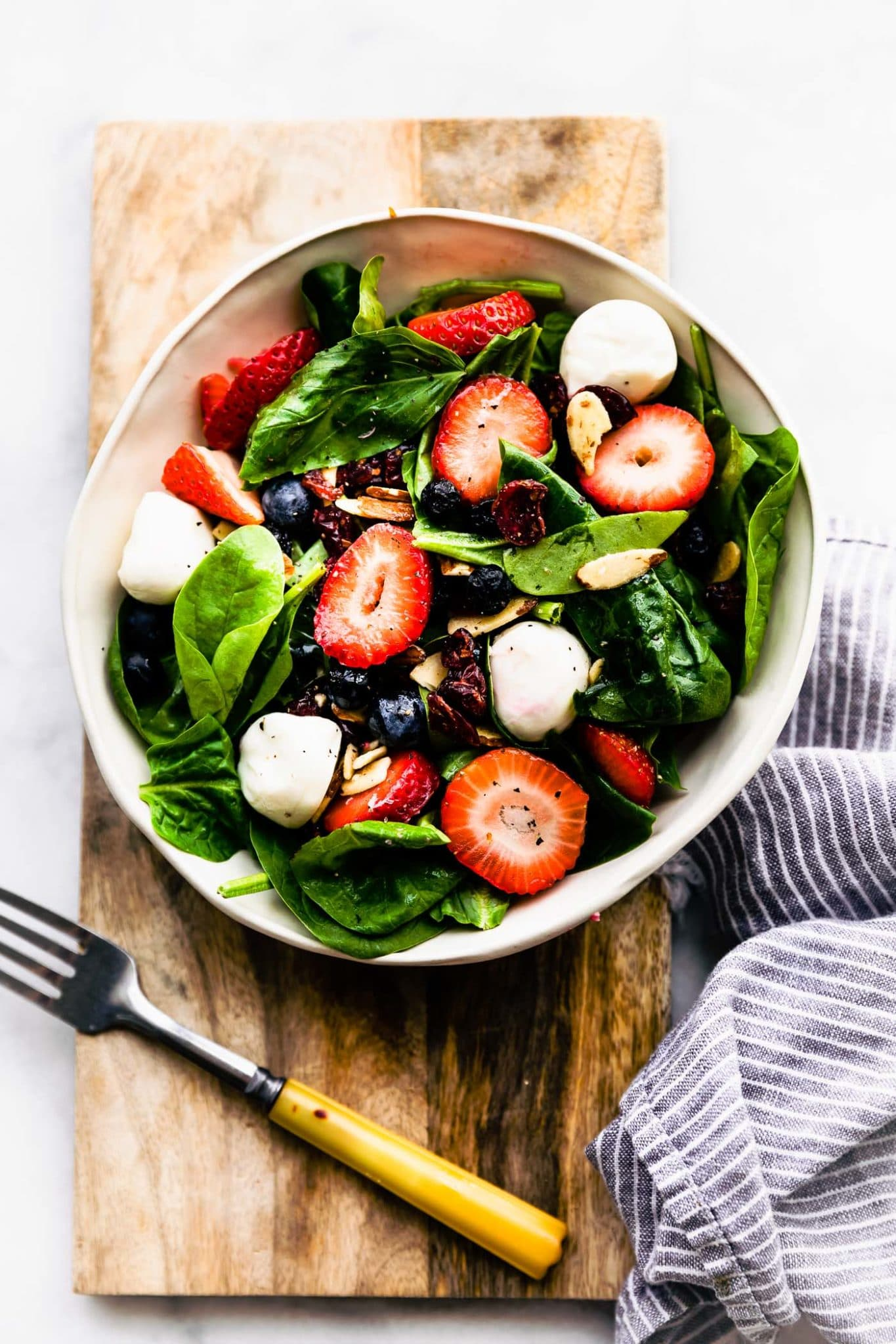 Overhead image of a bowl holding berry caprese salad on a wooden serving platter.