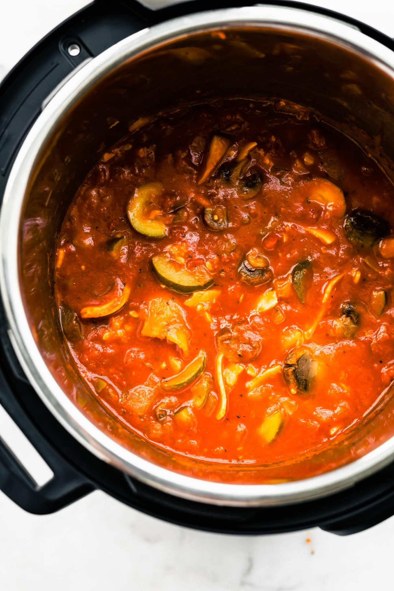 mushrroms and other veggies in an instant pot covred with a tomato sauce