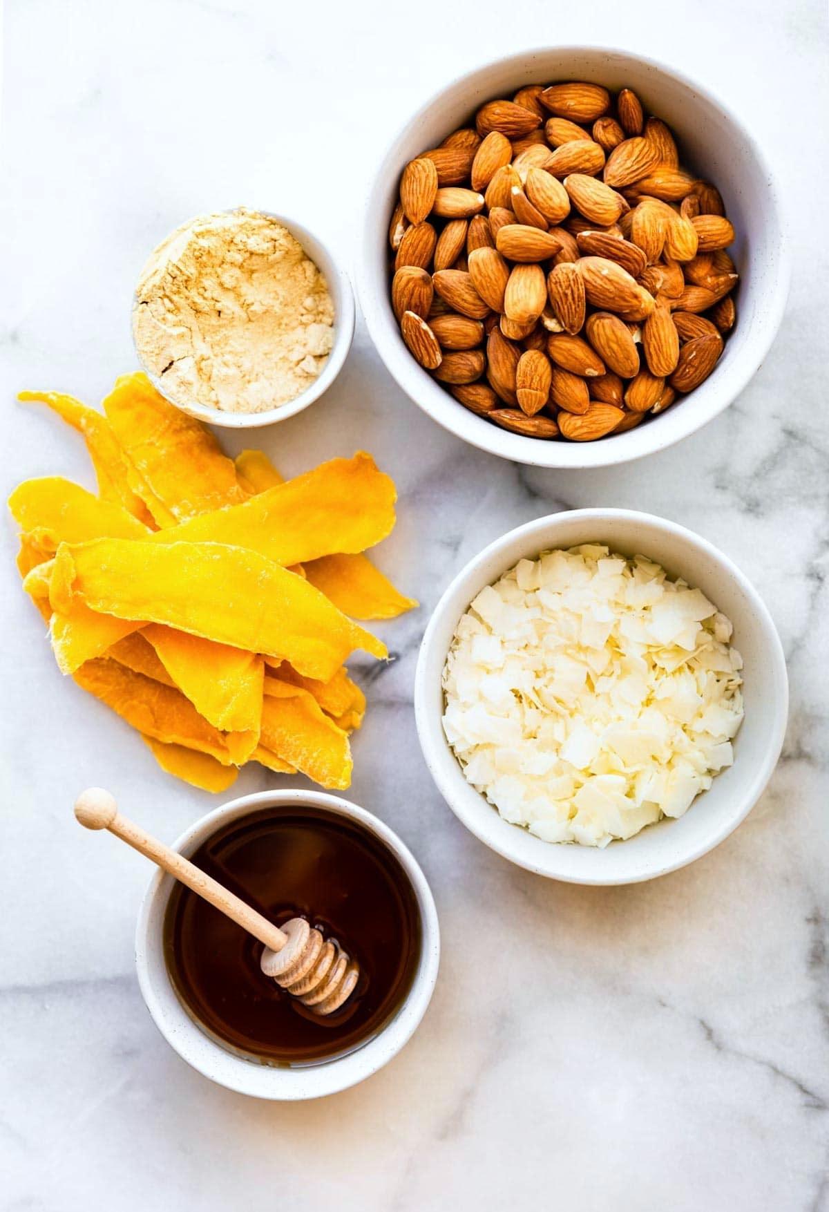 overhead shot of mango protein bar ingredients in bowls. Protein, almond, coconut, honey, mango