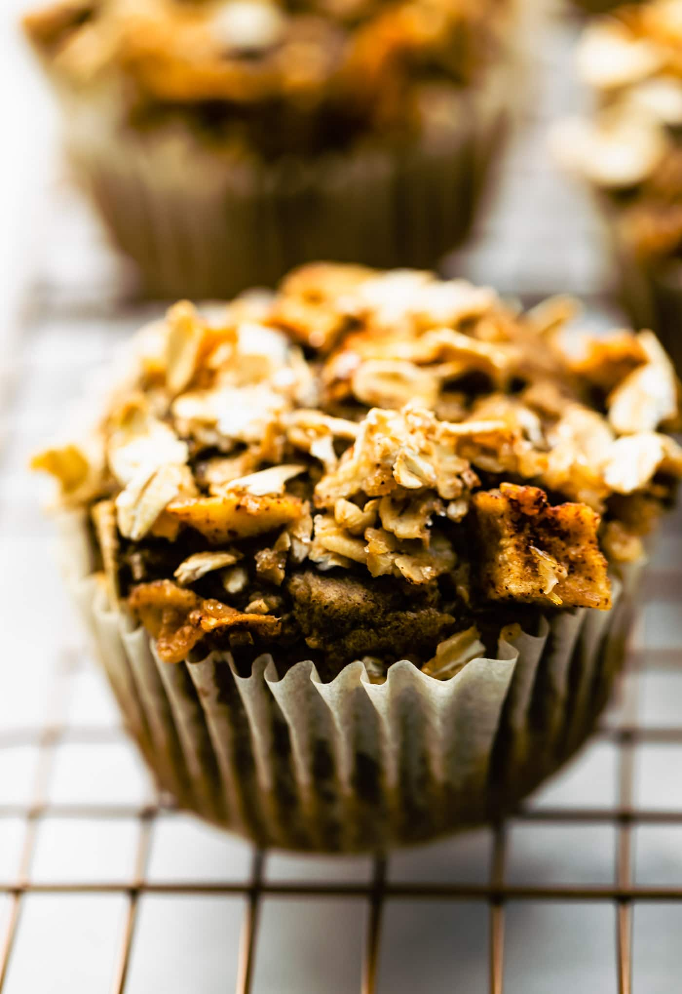 gluten free apple oatmeal muffins on a cooling rack in a muffin liner