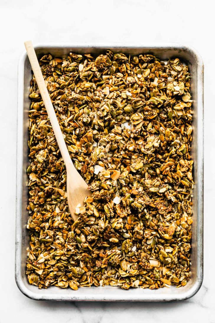 baked granola spread on a baking sheet with a wooden spoon