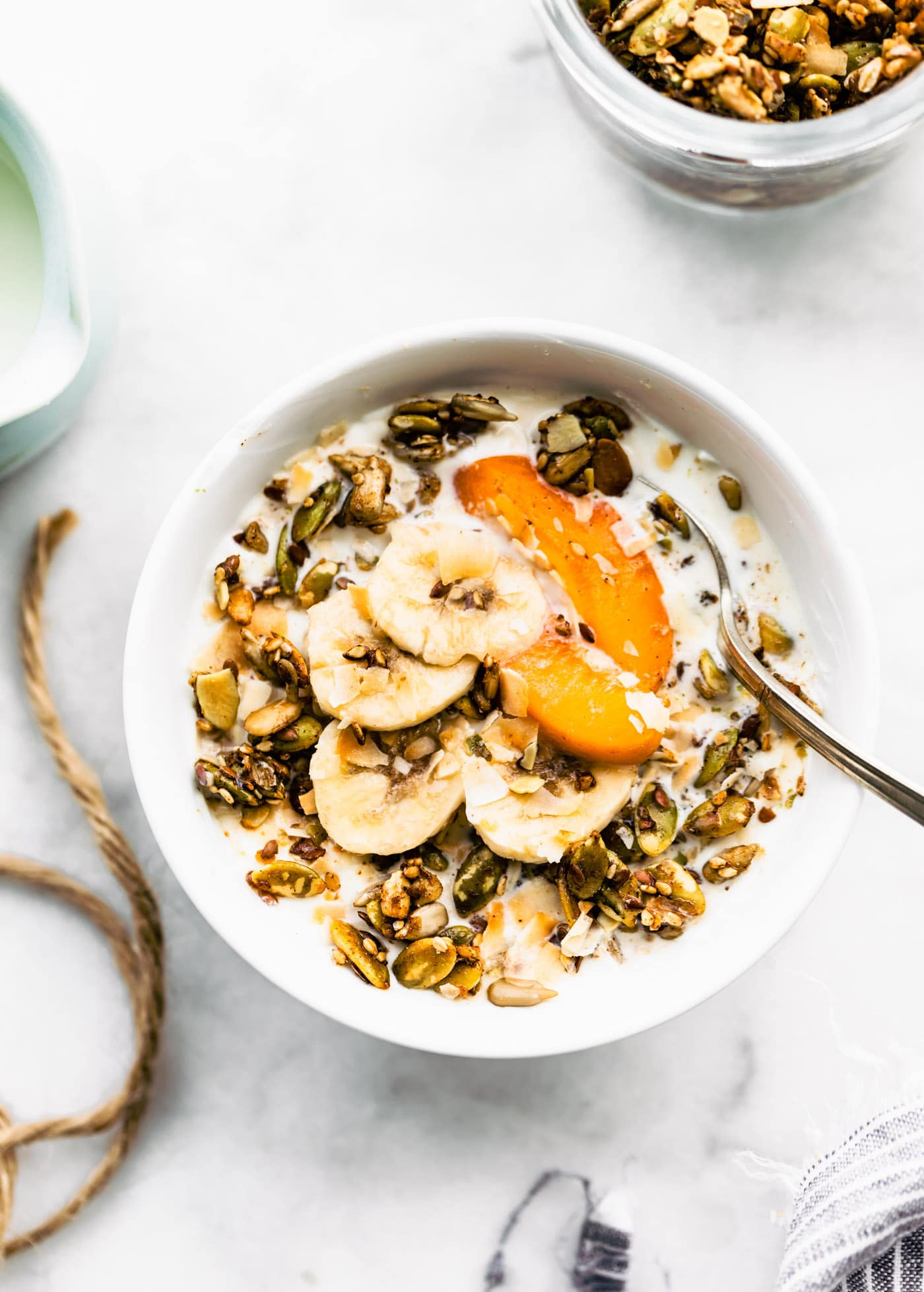pumpkin spice granola served as cereal in a bowl with fresh fruit and a spoon
