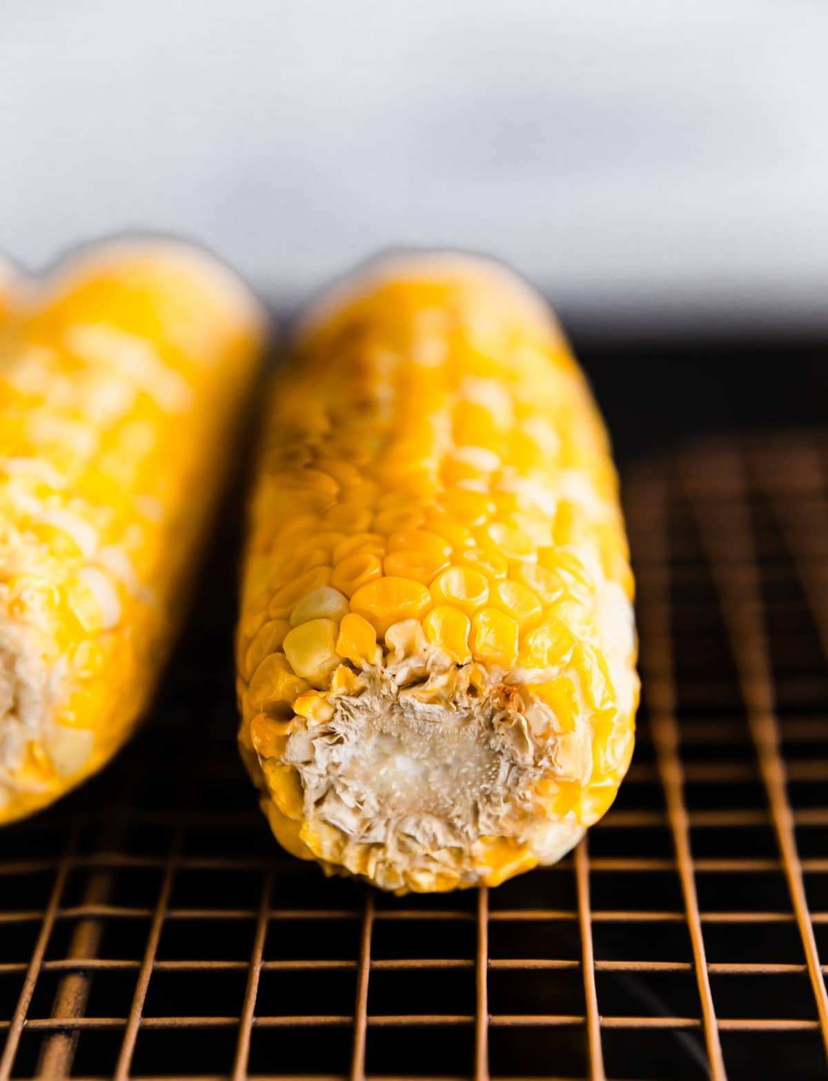 corn cobs on a metal grate for roasting