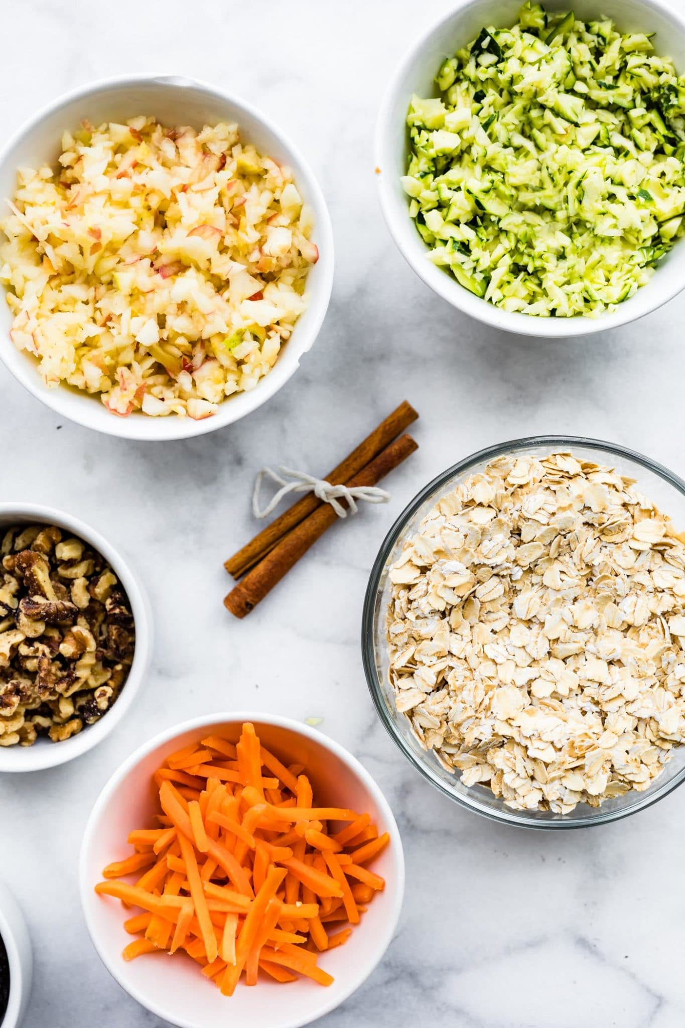 shredded zucchini, chopped apples, walnuts, shredded carrots, and cinnamon sticks on a white marble counter