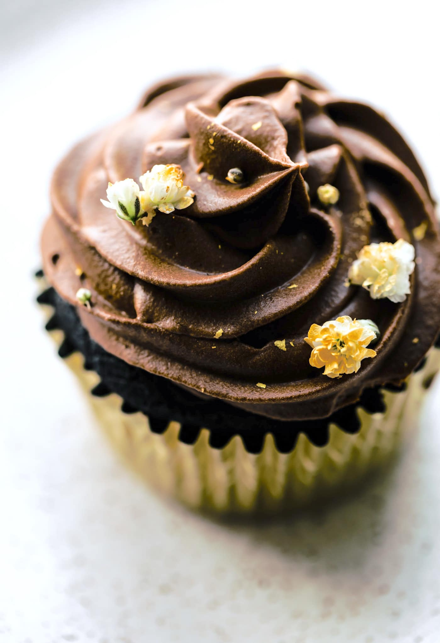 egg free chocolate cupcake with chocolate frosting and edible flowers on top