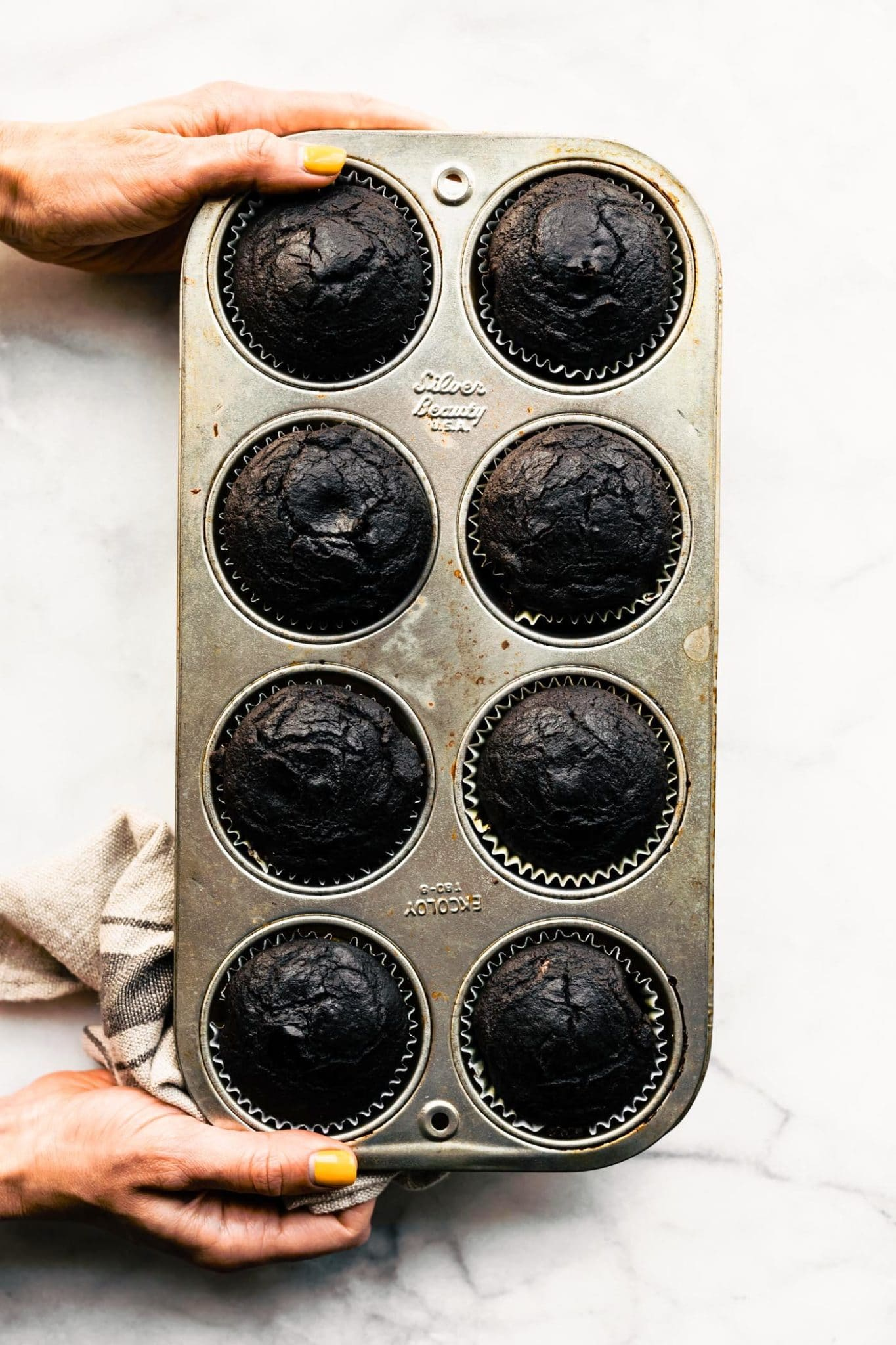 two hands holding a muffin tin full of baked egg free chocolate muffins