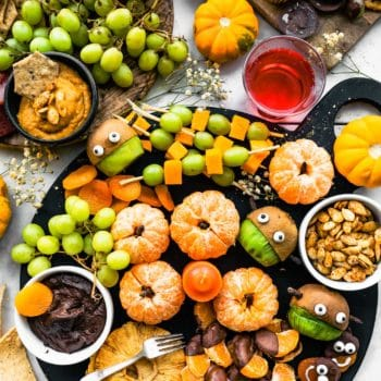 overhead photo of halloween snack board on black cheese board. Fruit, chocolates, grapes, pumpkin, and cupcakes. Dips in bowls
