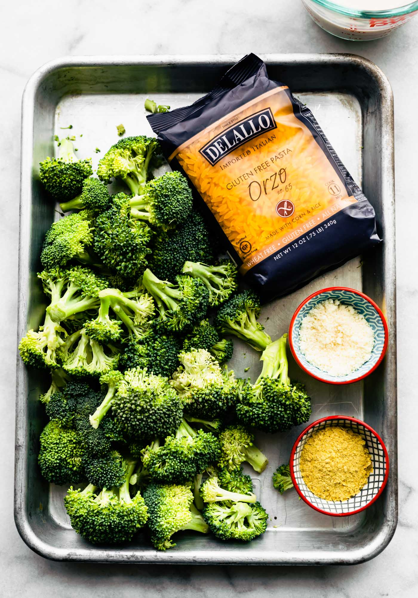 broccoli, orzo, arrowroot flour, and nutritional yeast in a baking dish for broccoli and cheese casserole
