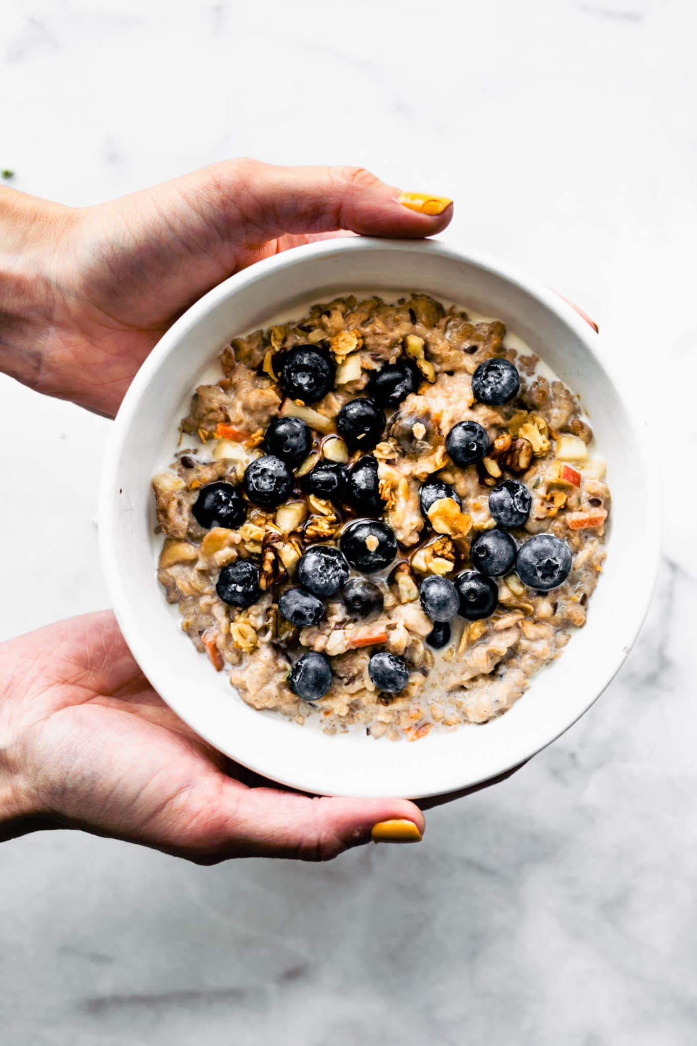 two hands holding a white bowl full of superfood oatmeal topped with fresh blueberries