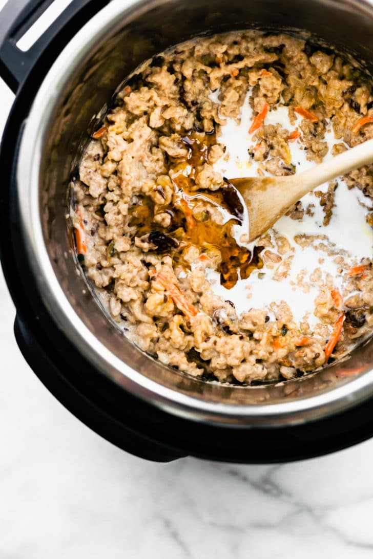 oatmeal in an instant pot with maple syrup being stirred in wtih a wooden spoon