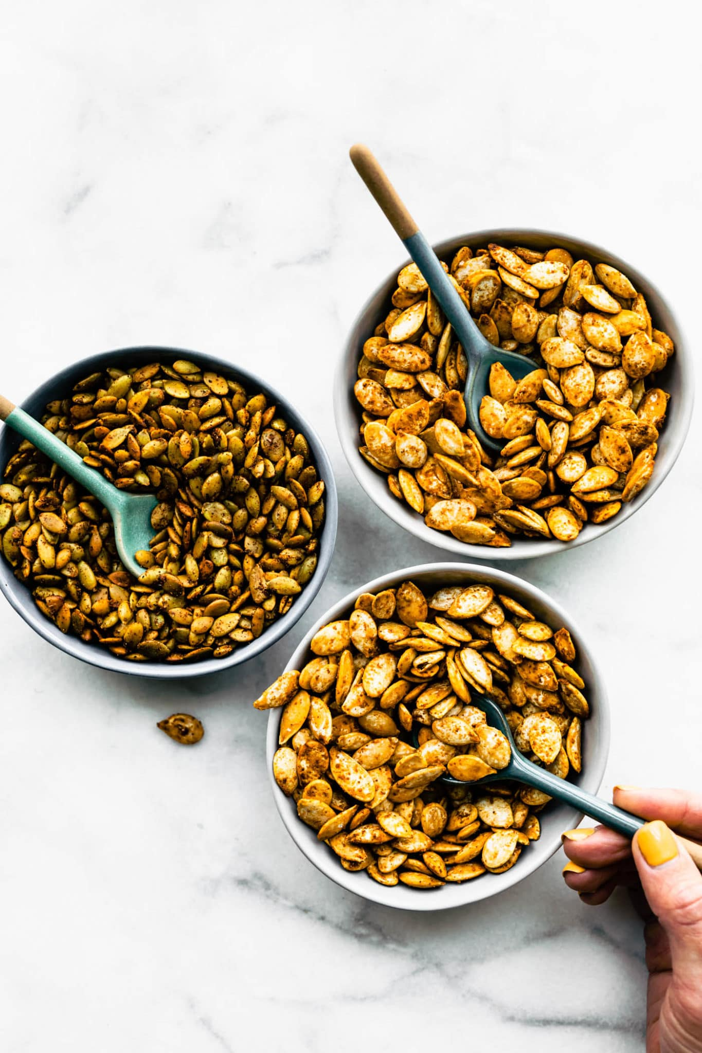 3 bowls of pumpkin seeds flavored different ways with spoons