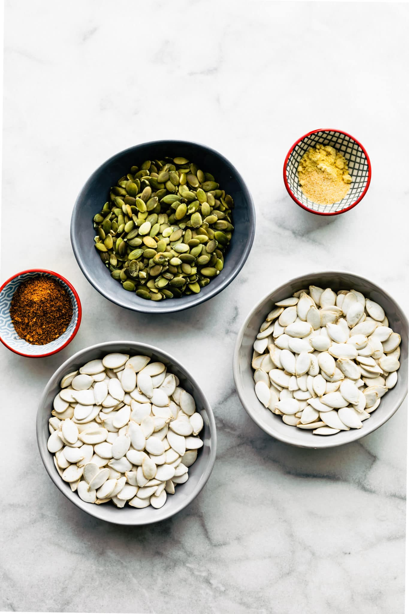 2 bowls of clean pumpkin seeds, 1 bowl of pepitas, and two small bowls with seasonings